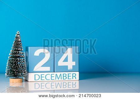 Eve Christmas. December 24th. Day 24 of december month, calendar with little christmas tree on blue background. Winter time. Empty space for text. New year concept.