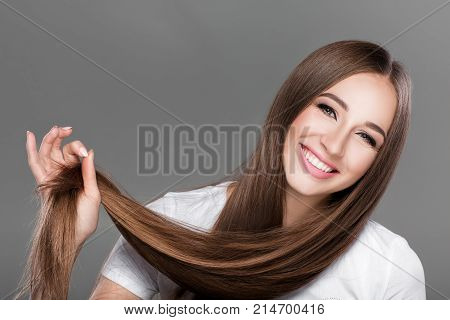 smiling beautiful brunette woman with shiny straight long hair. Care of  hair
