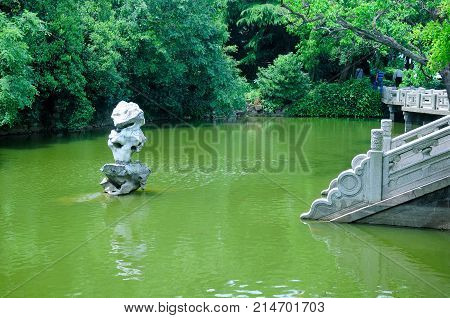 An outdoor rock sculpture over the green water as stone steps lead down to the water's edge on Fairy Island on Lake Tai (taihu) in Wuxi China in Jiangsu province.