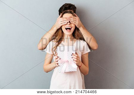 Portrait of a happy cheery girl holding present box while her boyfriend covers her eyes isolated over gray wall background