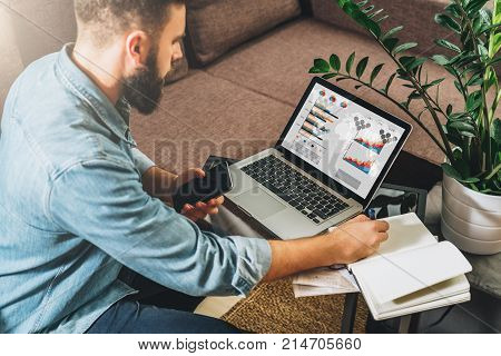 Man sits at table, working, holds smartphone, uses laptop with graphs, charts, diagrams on screen and makes notes in his notebook.Online marketing, education, e-learning, e-commerce. Startup, planning.