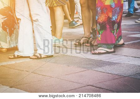 Group of casual men and women standing on paving in a low angle view of their feet in sandals jeans shorts and caftans or long summer skirts with the sun glow in the left corner