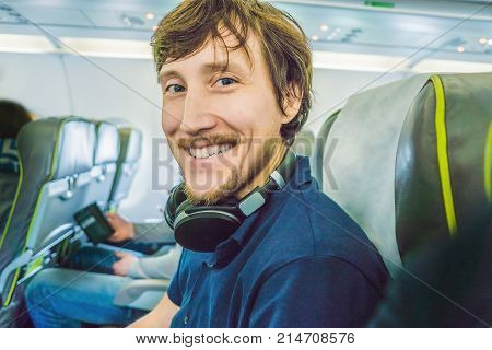 Passenger In Airplane Using Headphones. Man In Plane Cabin Listening To Music On Headphones.