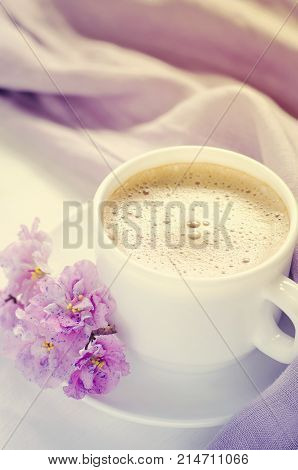 White cup of morning coffee or cappuccino and delicate pink, purple, lilac flowers. Mother's day concept. Cozy breakfast