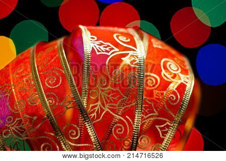 A beautiful red ribbon with several light in the background of diferent colors