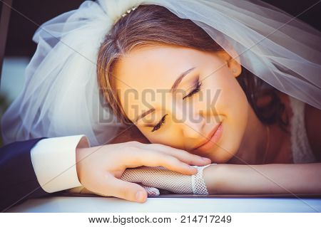 Tender Happy Bride In The Car, A Happy Woman In A Wedding Dress Laying Her Head On The Arm Of The Mo