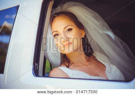 Tender Happy Bride In The Car, Happy Woman In A Wedding Dress Looking Out The Window, White Veil On