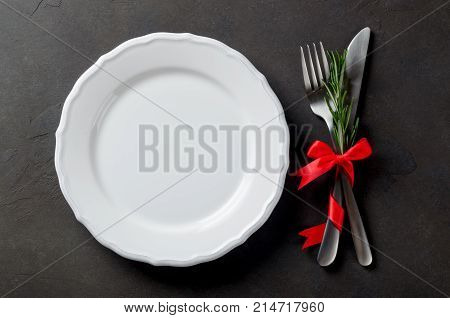 Festive set of cutlery knife and fork with red satin bow and rosemary a white dessert plate dark stone slate background top view copyspace