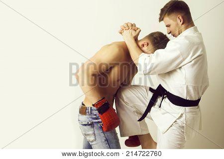Karate Athlete In Kimono Kicking Knee At Boxer