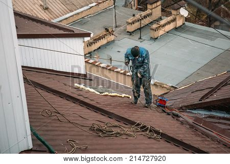 Unrecognised worker on modern roof, construction industry, view from above