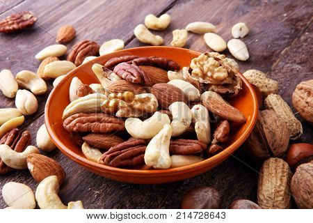 bowl with mixed nuts on wooden background. Healthy food and snack. Walnut pecan almonds hazelnuts and cashews