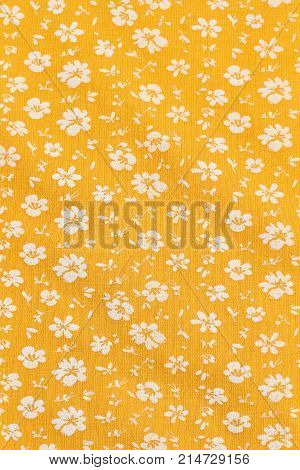 Textile wallpaper in floral print. Yellow fabric background in small white flowers. Small white flowers seamless pattern.