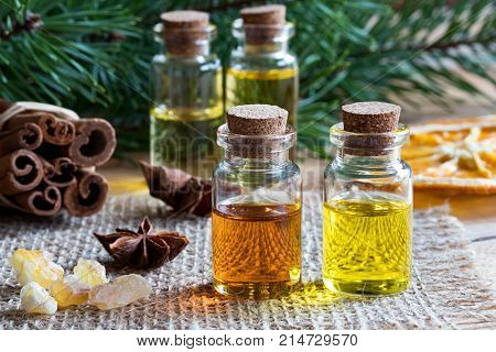 Selection Of Essential Oils With Star Anise, Cinnamon, Frankincense And Pine Branches