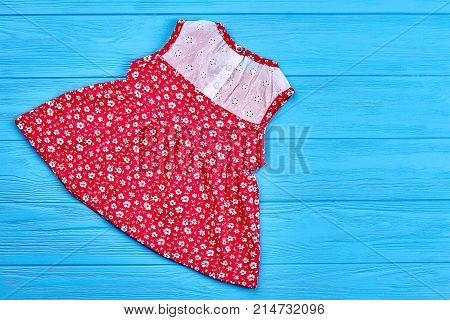 Dainty toddlers organic summer dress. Natural baby sleeveless dress and copy space, top view. Red cotton babby dress on sale.