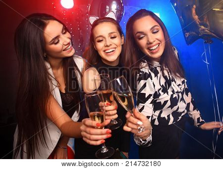 Beautiful girls having party fun, drinking champagne. Holidays, celebration, nightlife and people concept - smiling friends dancing in club poster