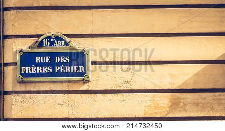blue parisian street sign on a stone wall where it is written in French - 16th arrondissement rue Perier brothers