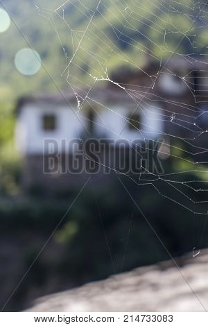 Spider's web in the foreground, old Bulgarian houses in the background, at Kosovo, Bulgaria
