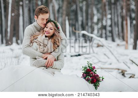 Bride and groom are hugging in the winter forest. Close-up. Winter wedding ceremony. . Artwork