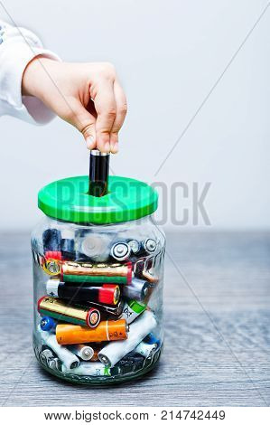 Kid hand filling the jar with used AA and AAA batteries