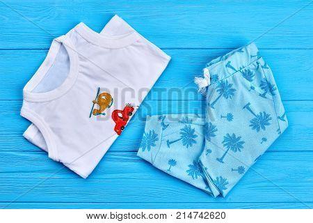 Set of patterned kids summer wear. New childs printed clothing on blue wooden background. Children summer garment.