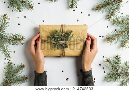 Woman hand holding gift box christmas decoration composition spruce fir brunch glitter stars on white festive table isolated. New year winter holiday xmas. Top view flat lay copy space