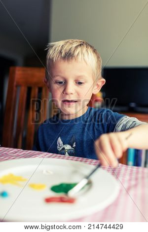 Young boy painting at home