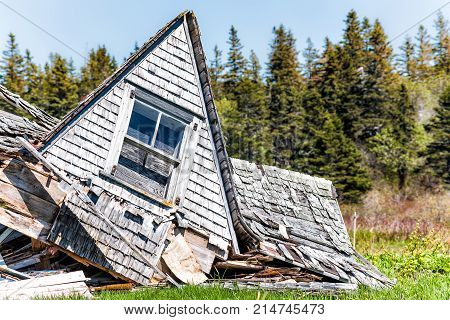 Destroyed Abandoned Wooden House In Village In Summer Collapsed In Green Field Closeup With Roof And