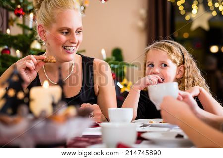 Parents and children celebrating Christmas with drinking coffee and X-mas cookies