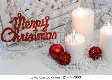 White burning candles and Merry Cristmas red gleaming inscription on a white wooden background