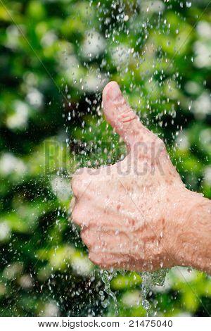 Thumb up under falling water horizontal