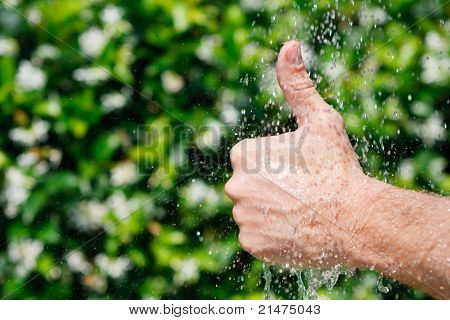 Thumb up under falling water