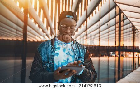 Handsome young black male student with white smile in glasses is checking his incoming messages via tablet pc; young handsome African guy waiting is chatting using digital pad near modern glass facade