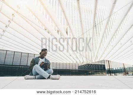 Young cheerful black student is sitting on the floor outdoor in modern bright urban settings and using digital pad to chat online with his friends; with copy space place for advertising or your text