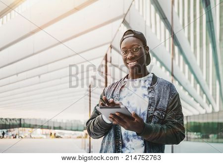Cheerful black guy in glasses with tablet pc outdoor near glass with copy space zone for message or advertising; young smiling Afro student outside of his college using his digital pad on a bright day