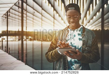 Young black man in jean jacket cap and glasses is using digital tablet to send a message while standing outside on street near contemporary building facade with copy space zone for logo or your text