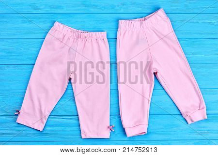 Lift pink pants for baby-girl. Toddler girl cotton trousers and breeches on blue wooden background. Infant girl summer trousers.