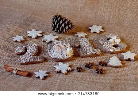 Holiday honey cookies stylized as wooden numbers 2 0 1 8 and stars laying near pine cones aniseed cinnamon sticks on sackcloth background