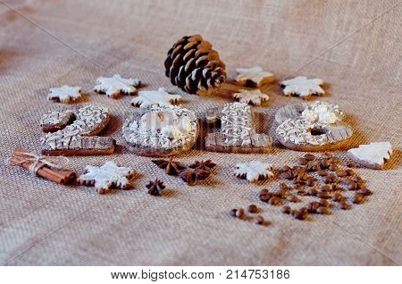 New year holiday honey cookies in shape of numbers stars laying on brown sackcloth background near pine cones aniseed cinnamon sticks coffee beans