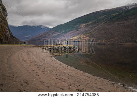 Woman standing on a shore and taking pictures of stunning scenery of norwegian fiord shore as seen from the shore in small village Flam, Norway