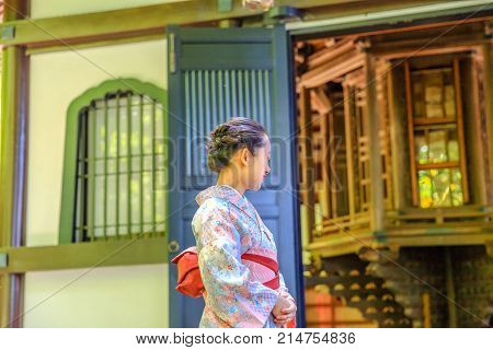 Kamakura, Japan - April 23, 2017: woman wearing in traditional japanese kimono in front of Kyozo or Sutra Archive inside Hase-dera Temple in Kamakura. Japanese culture and lifestyle. Spring season.