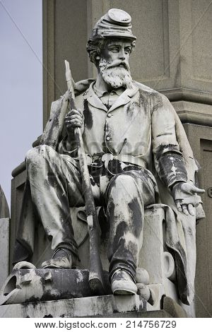 Gettysburg, Pennsylvania - September 9, 2009 - Vertical close up of a statue of a Civil War Soldier with long rifle set on a corner of the Memorial to Fallen Soldiers in Gettysburg National Cemetery, Pennsylvania on a bright afternoon in September.