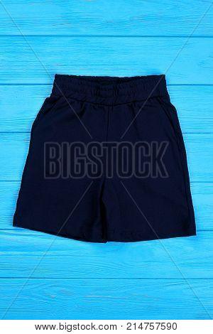 Little boys cotton shorts. Toddler boy sport shorts on blue wooden background. Textile short pants for children on sale.