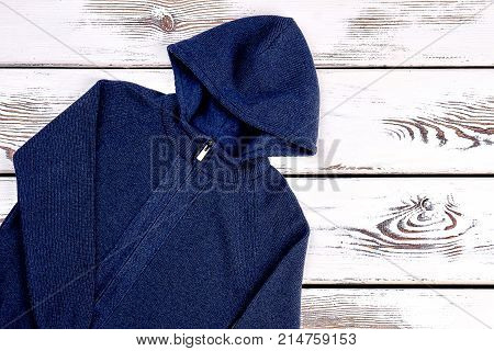 Dark blue knit cardigan. Brand hooded jacket for little boys on old wooden background. Childrens outfit on sale.