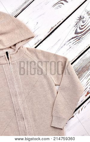Kids beige knitted hooded jacket. Cotton knitted hooded pullover for childrens, vintage wooden background.