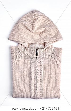 Beautiful beige hooded knitted cardigan. New cotton knit sweater for girls folded on white background. High quality knit outfit on sale.