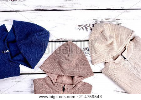 Collection of hooded knitted sweaters, top view. Cotton knit pullovers with hoodies for childrens on sale. Warm knit jumpers.
