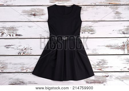 Black sleeveles short cotton dress. A-line black cotton girls dress on old wooden background. Girls casual black dress.