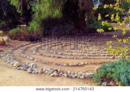 Maze of rocks creating a Labyrinth surrounded by trees and plants taken in a Zen Meditation Garden