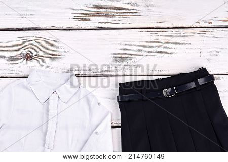 Elegant white shirt and black skirt. New white cotton blouse and black pleated skirt on sale. Girls school fashion.