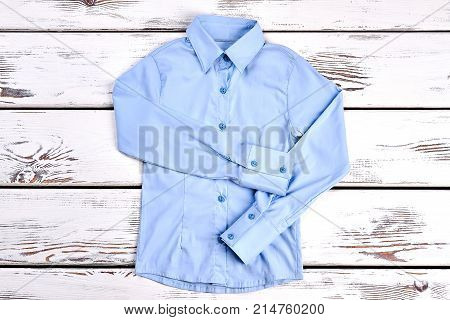 Light blue shirt with long sleeves. Formal shirt on wooden background. Beautiful buttoned blue shirt on sale.